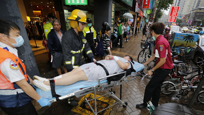 Paramedics remove a victim from a subway station exit after a knife attack on a subway in Taipei, Taiwan, Wednesday, May 21, 2014. A drunken university student wielding a knife attacked riders aboard a subway train in Taiwan's capital on Wednesday, killing three people and injuring nearly two dozen others, police and local media said. (AP Photo)