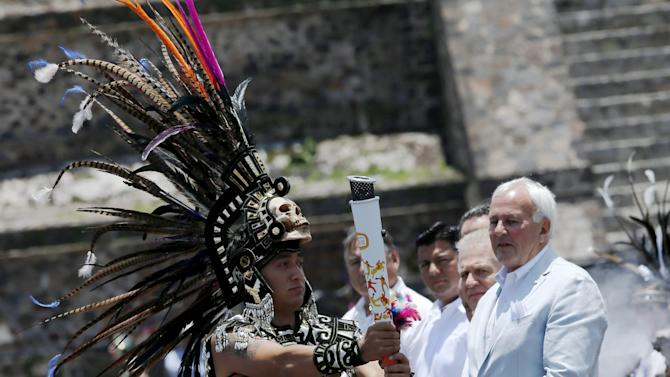 A Mexican dressed in prehispanic costumes holds up the torch of the Pan American Games as Chairman of the Toronto 2015 Pan-American Games organizing committee, David Peterson  looks on during the Ceremony of the Ignition of the New Fire