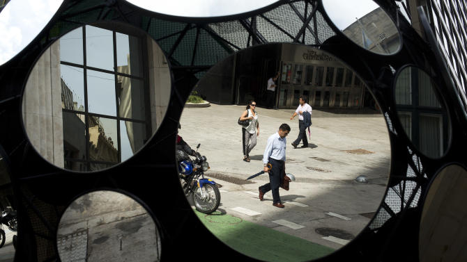 FILE - In this Tuesday, Jan. 28, 2014 file photo, office workers are reflected in a building's decorative mirrors in downtown Buenos Aires, Argentina. When Argentina fell into the economic abyss a decade ago after defaulting on its sovereign debt, Brazil suffered right along with it, nearly following its neighbor into insolvency. Now, with Argentina's economy again facing a currency plunge and inflation spike, its ability to inflict economic damage on Brazil has greatly diminished. (AP Photo/Victor R. Caivano, File)