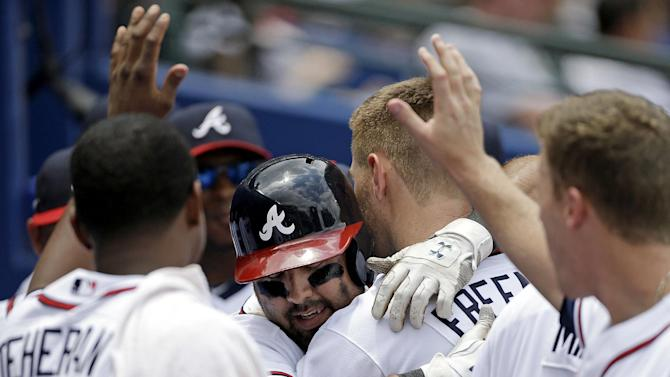 Atlanta Braves' Gerald Laird, center, is embraced by teammate Freddie Freeman in the dugout after hitting a home run in the sixth inning of a baseball game against the Pittsburgh Pirates, Wednesday, June 5, 2013, in Atlanta. (AP Photo/David Goldman)
