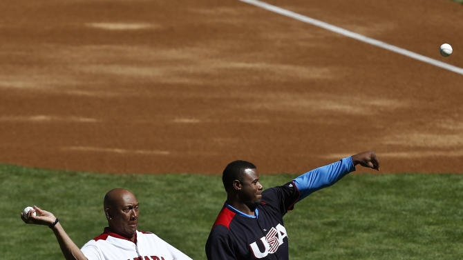 Former MLB players representing their countries Ferguson Jenkins, left, of Canada, and Ken Griffey, Jr., of the United States, throw out the first pitch prior to a World Baseball Classic baseball game between Canada and the United States on Sunday, March 10, 2013, in Phoenix. (AP Photo/Ross D. Franklin)