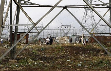 High voltage electrical pylons stand at a slum on the outskirts of Kenya's capital Nairobi