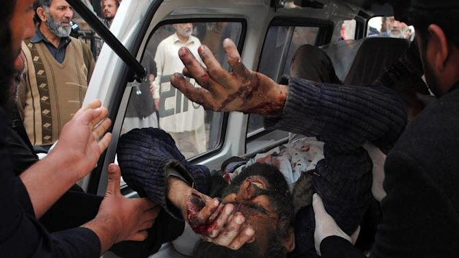Pakistani volunteers rush an injured person to a local hospital after a bombing in Peshawar, Pakistan on Monday, Feb 18, 2013. Militants wearing suicide vests and disguised as policemen attacked the office of a senior political official in northwestern Pakistan on Monday, killing several people, police and hospital officials said. (AP Photo/Sohail Iqbal)