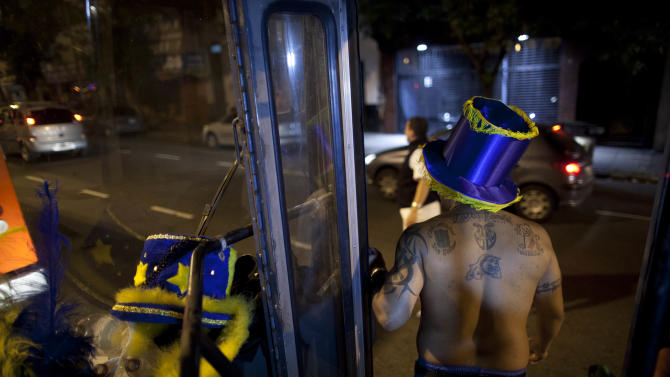 """A member of the murga """"Los amantes de La Boca"""" stands on bus as he heads to carnival celebrations in Buenos Aires, Argentina, Saturday, Feb. 2, 2013. Argentina's carnival celebrations may not be as well-known as the ones in neighboring Uruguay and Brazil, but residents of the nation's capital are equally passionate about their """"murgas,"""" or traditional musical troupes. The murga """"Los amantes de La Boca,"""" or """"The Lovers of The Boca"""" is among the largest, with about 400 members. It's a reference to the hometown Boca Juniors, among the most popular soccer teams in Argentina and the world. In background, Boca Juniors soccer team's stadium. (AP Photo/Natacha Pisarenko)"""