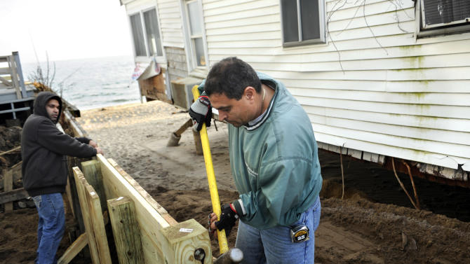 In this Dec. 4, 2012 photo, builders Reginaldo Ferreira, left, and Liudmil Petrov of Russe Builders construct a wall to protect a beachfront home in Fairfield, Conn.  The national economy is expected to absorb the blow from Sandy with little long-term damage, but in the short term, at least, Sandy is introducing dramatic booms and busts across the Northeast. The effects vary widely across industries, bringing banner years for some while pushing others toward economic ruin. (AP Photo/Jessica Hill)