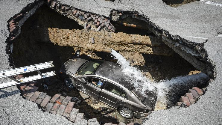 AP10ThingsToSee - This photo provided by the Toledo, Ohio Fire and Rescue Department shows a car at the bottom of a sinkhole caused by a broken water line in Toledo, Ohio on Wednesday, July 3, 2013. Police say the driver, 60-year-old Pamela Knox of Toledo, was shaken up and didn't appear hurt but was taken to a hospital as a precaution. (AP Photo/Toledo, Ohio Fire and Rescue Department, Lt. Matthew Hertzfeld, File)