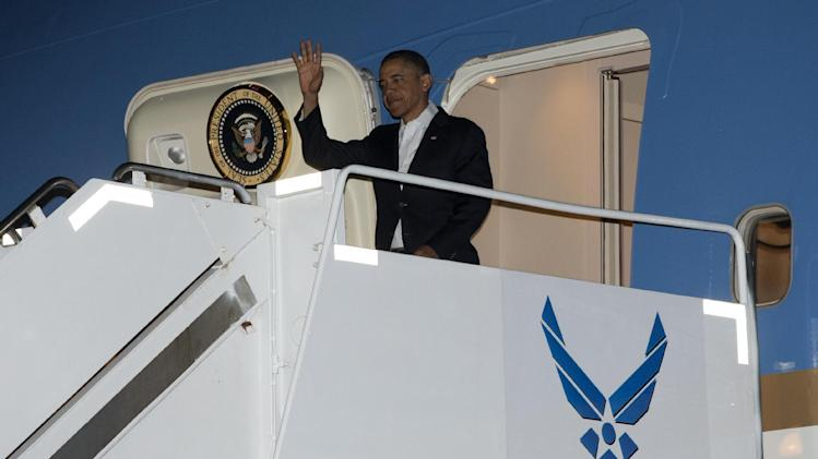 President Barack Obama waves as he gets off Air Force One upon his arrival at Joint Base Pearl Harbor-Hickam, Honolulu, Hawaii, Wednesday, Jan. 2, 2013. The president is back in Hawaii for vacation after a tense, end-of-the-new-year standoff with Congress over the fiscal cliff.  (AP Photo/Carolyn Kaster)
