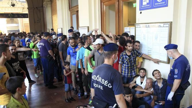Hungarian police speak to people queueing to buy train tickets a the railway station in Budapest