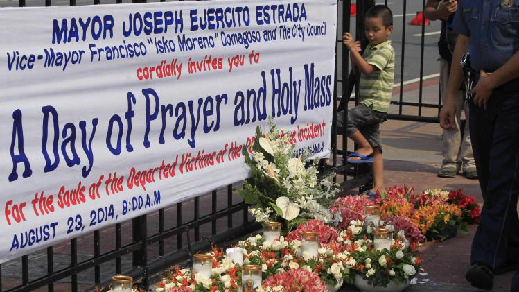 Boy looks at the candles and flowers offered in front of a streamer observing the fourth anniversary of the 2010 hostage crisis, at Luneta park in metro Manila