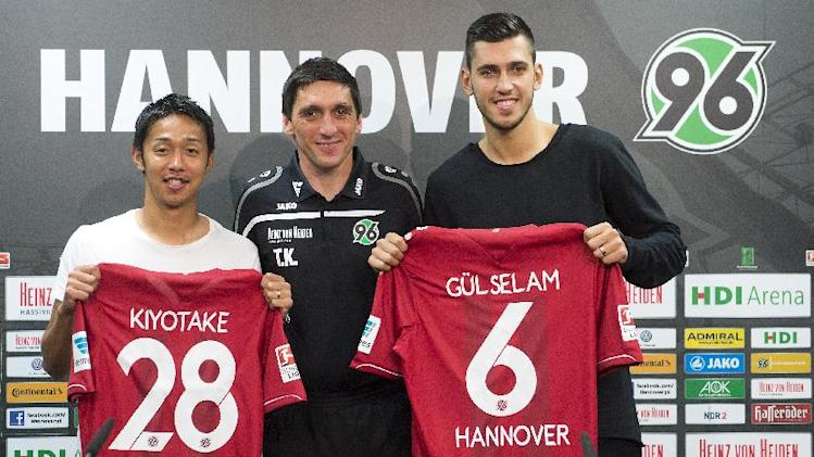 Head coach of Bundesliga soccer club Tayfun Korkut is framed by Hannover's new players, Japan'.s , Hiroshi Kiyotake, left, and Turkey's Ceyhun Gulselam, right, after a press conference in Hannover, northern Germany Friday July 25, 2014. Hannover  has signed Japan attacking midfielder Hiroshi Kiyotake from relegated Bundesliga rival Nuremberg. Kiyotake signed a four-year contract. No details were released