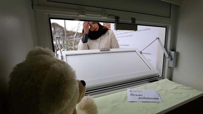 "Galina Murzakayeva, a coordinator for Kolybel Nadezhdy (Cradle of Hope), a non-governmental organization, opens the baby box in Kirishi, an industrial town of 50,000 located 100 kilometers (60 miles) east of St. Petersburg, Russia, Wednesday, Oct. 31, 2012. A box in which parents can leave their babies anonymously and without any legal risk opened Wednesday in the town of Kirishi in northwestern Russia, in part of an effort activists hope will save many young lives. The box in Kirishi is the tenth such facility in Russia, just a fraction of what experts think is needed to help save hundreds of babies abandoned by their mothers each year. The sign reads ""A letter to parents."" (AP Photo/Dmitry Lovetsky)"