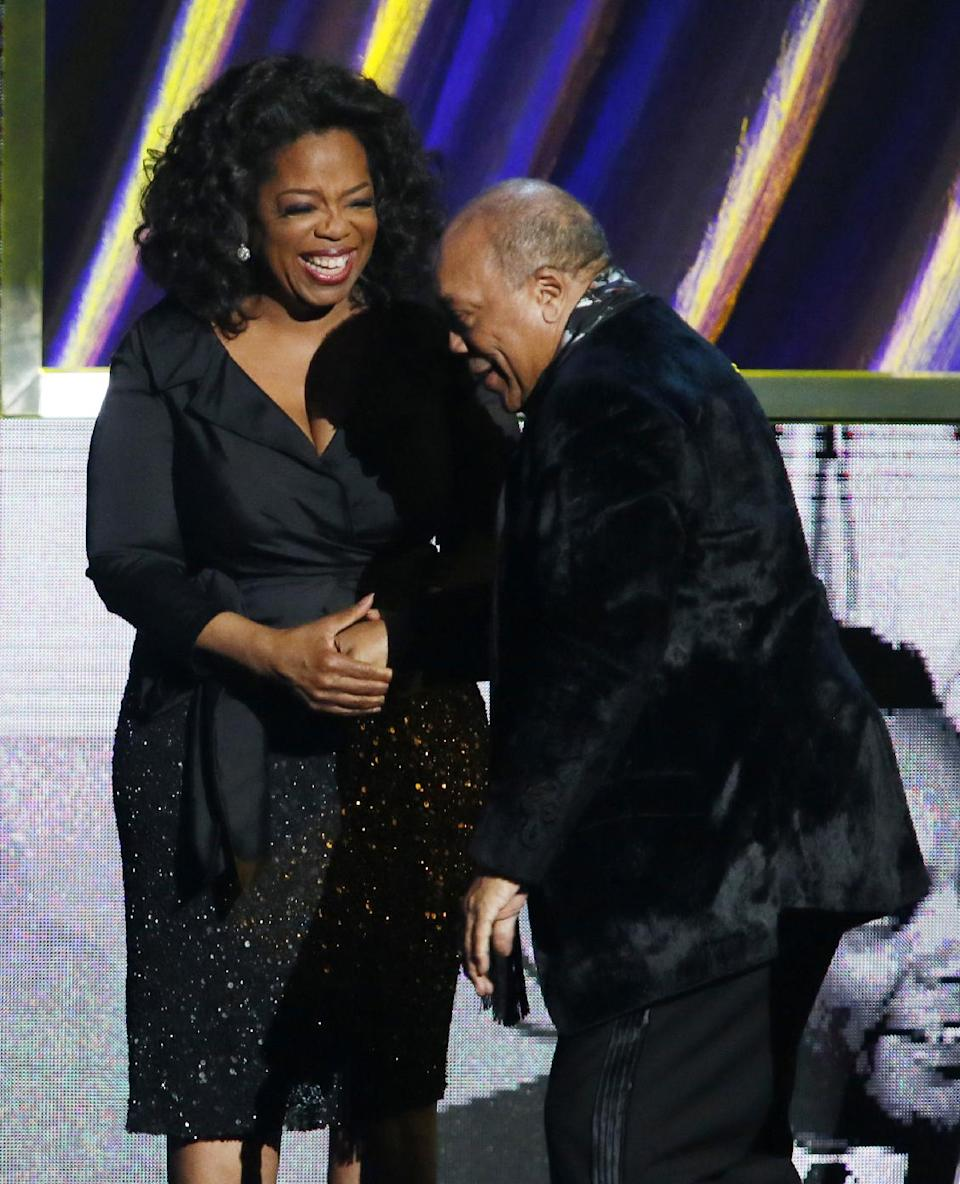 Oprah Winfrey, left, leads inductee Quincy Jones on the stage after as Jones during the Rock and Roll Hall of Fame Induction Ceremony at the Nokia Theatre on Thursday, April 18, 2013 in Los Angeles. (Photo by Danny Moloshok/Invision/AP)