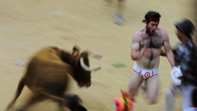 A reveler  tries to escape a bull in the bull ring, at the end of third running of the bulls at the San Fermin fiestas, in Pamplona northern Spain, Monday, July 9, 2012. (AP Photo/Alvaro Barrientos)