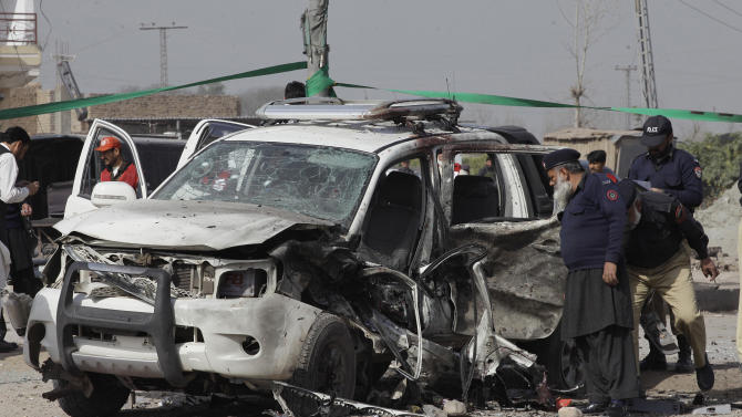 Pakistani security officials examine a vehicle targeted by a suicide attacker in Peshawar, Pakistan on Thursday, March 15, 2012. The attack killed a senior police officer and wounded others. (AP Photo/Mohammad Sajjad)