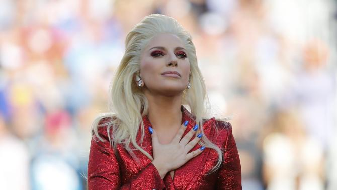 Lady Gaga places her hand over her heart after singing the U.S. National Anthem before the start of the NFL's Super Bowl 50 football game between the Carolina Panthers and the Denver Broncos in Santa Clara