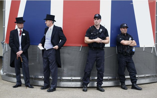 Racegoers wearing top hats and tails stand next to police officers during Ladies' Day at the Royal Ascot horse racing festival at Ascot