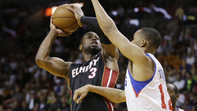 Philadelphia 76ers' Evan Turner (12) tries to block Miami Heat's Dwyane Wade (3)  during the first half of a NBA basketball game in Miami, Friday, March 8, 2013. (AP Photo/J Pat Carter)