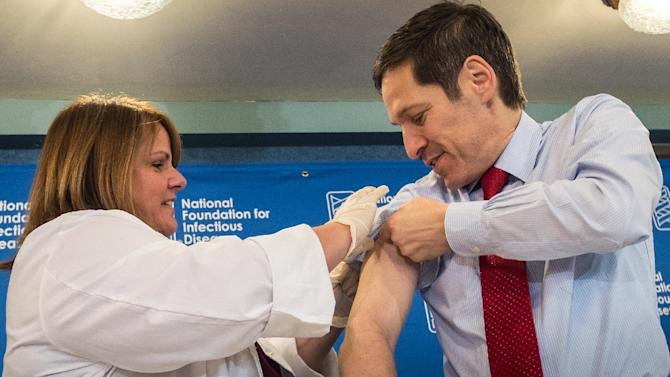 """Dr. Thomas Frieden, director of the Centers for Disease Control and Prevention, receives a flu shot from Sharon Bonadies at the conclusion of a news conference at the National Press Club in Washington, Thursday, Sept. 18, 2014.  """"Vaccination is the single most important step everyone 6 months of age and older can take to protect themselves and their families against influenza,"""" said Frieden.  Influenza hospitalized a surprisingly high number of young and middle-aged adults last winter, and this time around the government wants more of them vaccinated. (AP Photo/J. David Ake)"""