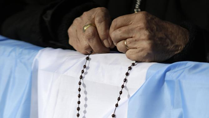 """A faithful holds a rosary over an Argentine flag in St. Peter's square at the Vatican on the occasion of the celebration of the Easter mass Sunday, March 31, 2013. """"Our daily problems and worries can wrap us up in ourselves, in sadness and bitterness, and that is where death is,"""" he said. """"Let the risen Jesus enter your life, welcome him as a friend, with trust: he is life!"""" said Pope Francis during the Easter vigil. (AP Photo/Andrew Medichini)"""