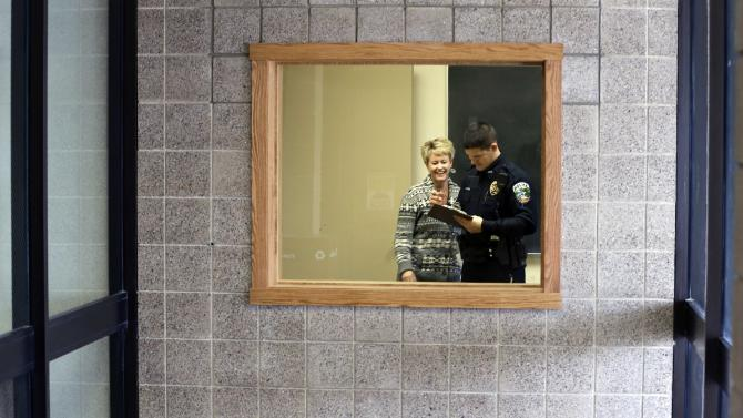 In a photo made Thursday, Feb. 21, 2013, police officer Jeff Strack talks with principal Stacy DeCorsey,left, in a room being prepared for police as seen from the school entry at Jordan Elementary School in Jordan, Minn. In what is believed to be the first of its kind nationwide, the small city south of Minneapolis is taking school security to a new level by setting up satellite offices inside the public school buildings. (AP Photo/Jim Mone)