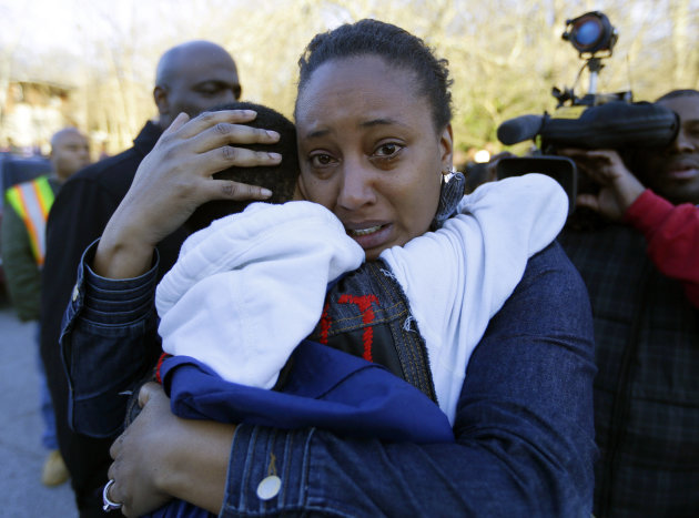 A woman comforts a child after after a shooting at an Price Middle school in Atlanta Thursday, Jan. 31, 2013. A 14-year-old boy was wounded outside the school Thursday afternoon and a fellow student w