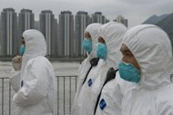 Rescue workers wearing environmental suits look on while participating in the Daya Bay Contingency Plan exercise in Hong Kong. The Hong Kong government tested its capacity to respond to a serious nuclear accident at the Daya Bay station, just 20 kms (12 miles) east of the city