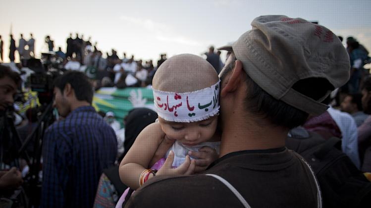 "A volunteer of Pakistani Muslim cleric Tahir-ul-Qadri listens to his leader holding his baby with headband reads ""revolution or martyrdom,"" during a sit-in protest near the parliament building in Islamabad, Pakistan, Thursday, Aug. 28, 2014. Pakistani police have registered a murder case against Prime Minister Nawaz Sharif, his brother Shahbaz, key cabinet members and senior officials on charges of abetting 14 murders of the supporters of a fiery cleric who has been leading for two weeks thousands of anti-government protests in capital Islamabad. (AP Photo/B.K. Bangash)"