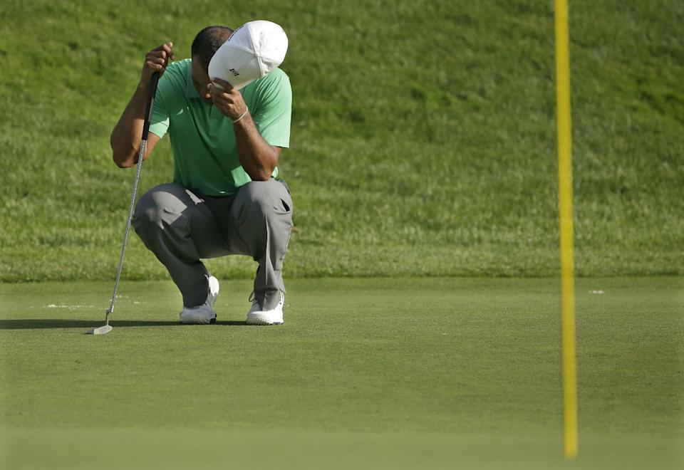 Tiger Woods crouches on the 17th green during the second round of the PGA Championship golf tournament at Oak Hill Country Club, Friday, Aug. 9, 2013, in Pittsford, N.Y. (AP Photo/Charlie Riedel)