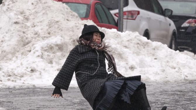 A woman falls while slipping on ice during freezing rain on Roosevelt Island, a borough of Manhattan in New York
