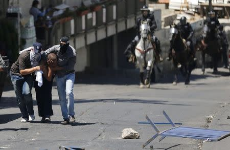 Undercover Israeli police officers detain a Palestinian suspected of throwing stones in the East Jerusalem neighbourhood Wadi al-Joz during a protest against the Israeli offensive on Gaza