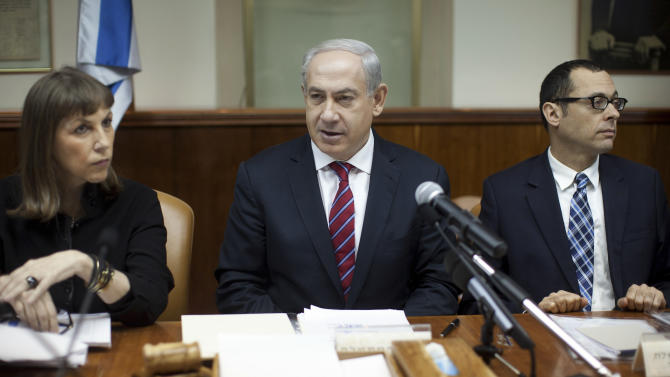 Israeli Prime Minister Benjamin Netanyahu, center, heads the weekly cabinet meeting in his Jerusalem office, Sunday, Jan. 6, 2013. Netanyahu said Sunday he will erect a fortified fence on the border with Syria to protect against radical Islamist forces that he claims have taken over the area. (AP Photo/Uriel Sinai, Pool)