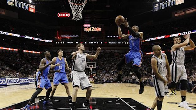 Thunder guard Russell Westbrook (0) drives to the basket as San Antonio Spurs forward Tiago Splitter (22) looks on during the second half at AT&T Center (Reuters)