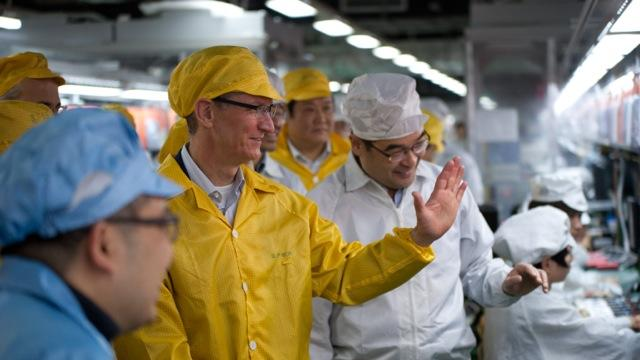 In this March 28, 2012 photo provided by Apple, Inc., Apple CEO Tim Cook, center, visits the iPhone production line at the newly-built manufacturing facility Foxconn Zhengzhou Technology Park, which employs 120,000 people. A report released Thursday, March 29, by the Washington-based Fair Labor Association says Hon Hai Precision Industry Co., the Taiwanese company that runs Apple's factories in mainland China, has committed to reducing weekly work time to the legal Chinese maximum of 49 hours. (AP Photo/Apple)