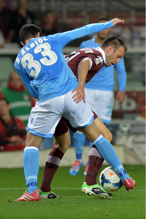 Torino forward Riccardo Meggiorini, right, challenges for the ball with Napoli defender Raul Albiol during a Serie A soccer match, at the Olympic  stadium, in Turin, Italy, Monday, March 17, 2014