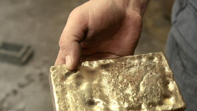 FILE - In this Jan. 17, 2008 file photo, Brian Goodrich shows a  gold brick he removed from the  mold  at the Oxford Assaying and Refining Corp. in Anchorage. In 2010 gold surpassed $1400 an ounce for the first time.  (AP Photo/ Al Grillo, file)