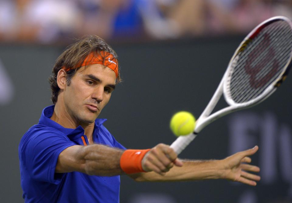 Roger Federer, of Switzerland, returns a shot to Rafael Nadal, of Spain, during their match at the BNP Paribas Open tennis tournament on Thursday, March 14, 2013, in Indian Wells, Calif. (AP Photo/Mark J. Terrill)
