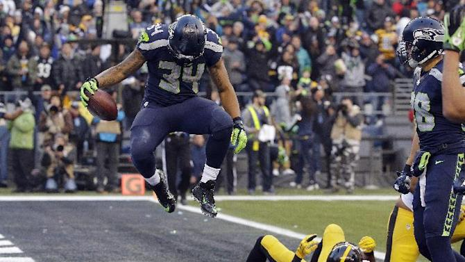 Seattle Seahawks' Thomas Rawls (34) jumps after scoring a touchdown as Pittsburgh Steelers' Mike Mitchell lies in the end zone in the second half of an NFL football game, Sunday, Nov. 29, 2015, in Seattle. (AP Photo/Ted S. Warren)