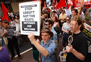 Protesters carry placards at a 'Welcome Refugees' rally…