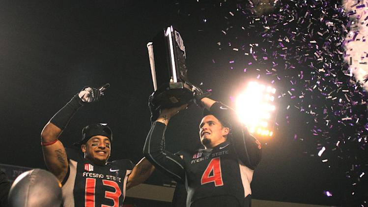 Fresno State's Derek Carr and Derron Smith celebrate the Mountain West championship in the second half of an NCAA college football game in Fresno, Calif., Saturday, Dec. 7, 2013