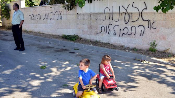 """An Israeli-Arab and children are seen on a street next to a graffiti in the village of Abu Gosh near Jerusalem, Tuesday, June 18, 2013. Israeli police have launched an investigation to find perpetrators who vandalized cars and sprayed hate graffiti in an Arab town near Jerusalem. The Hebrew graffiti reads, """"Racism or assimilation"""" and """"Arabs out."""" (AP Photo/Mahmoud Illean)"""