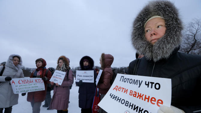 "A demonstrator holds a poster reading ""Children are more important than officials"" during a protest against plans to shut down City Hospital No. 31 in St. Petersburg, Russia, Wednesday, Jan. 23, 2013. Some 1,500 thousand people gathered for a rally against plans to shut a clinic specialized in treating children with cancer in order to turn it into a medical center for the nation's top judges. The authorities intention to turn City Hospital No. 31 into a clinic that would exclusively serve judges of Russia's top courts, which are being relocated to St.Petersburg from Moscow, has caused a strong public dismay. On Wednesday, St.Petersburg Governor's office said that the hospital will continue to serve patients as before and there is no plan to change its location or profile.  (AP Photo/Dmitry Lovetsky)"