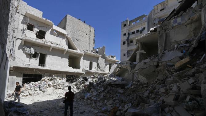Residents inspect a site damaged by what activists said were barrel bombs dropped by forces loyal to Syria's President Assad in Al-Fardous