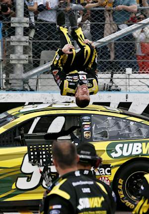 Carl Edwards performs a flip in front of his crew as he celebrates winning the NASCAR Sprint Cup Series auto race, Sunday, March 3, 2013, in Avondale, Ariz. (AP Photo/Ross D. Franklin)