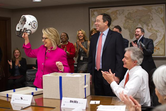 This photo provided by the United States Department of State shows Secretary of State Hillary Rodham Clinton holding up a football helmet presented to her at the State Department in Washington, Monday