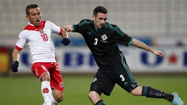 Northern Ireland's Daniel Lafferty (R) shoots the ball as Malta's Andrew Cohen (L) tries to block during their international friendly soccer match in Ta'Qali, outside Valletta, February 6, 2013. (Reuters)