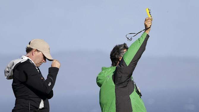 A wind gauge, right, is being held up before the first round at the Tournament of Champions PGA golf tournament, Sunday, Jan. 6, 2013, in Kapalua, Hawaii. Play was to have started two days earlier, but was delayed because of rain and high winds. (AP Photo/Elaine Thompson)