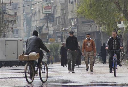 People walk as others ride on a bicycle along a street in Arbeen, in the eastern Damascus suburb of Ghouta