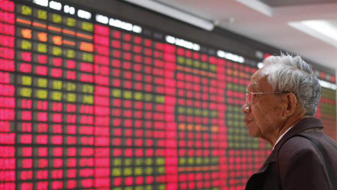 An investor looks at the stock price monitor at a private securities company Monday, Nov. 25, 2013 in Shanghai, China. Asian stock markets rose Monday after Wall Street posted its seventh straight week of gains and a nuclear deal between world powers and Iran boosted sentiment. (AP Photo)