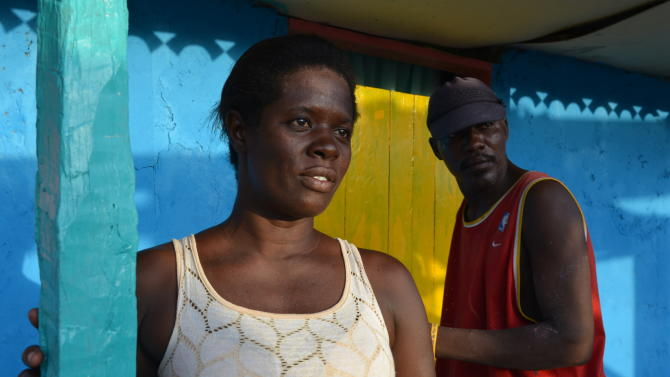 In this Oct. 24, 2014 photo, Marie-Ange Baltisima, left, a coffee vendor and mother of four girls in the fishing village of Cotes-de-Fer in southern Haiti, stands in front of a freshly-painted house where she and her neighbors hosted the country's tourism minister during a recent Cabinet retreat in the area. Haitian President Michel Martelly's government is pursuing plans for Haiti's biggest tourism development ever in the poor coastal area and officials are trying to line up investors to help spur an economic revival. As the country enjoys a period of relative tranquility after years of turmoil, Haitian officials say they see ambitious tourism projects as key to economic development. (AP Photo/David McFadden)