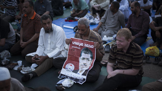A supporter of Egypt's ousted President Mohammed Morsi holds a placard depicting the former leader during a protest near Cairo University in Giza, Egypt, Sunday, July 28, 2013. Setting the stage for more confrontation, the military-installed interim president, Adly Mansour, gave Prime Minister Hazem el-Biblawi the power to grant the military the right to arrest civilians in what government officials said could be a prelude to a major crackdown on Morsi's supporters or Islamic militants who have stepped up attacks against security forces in the Sinai Peninsula. (AP Photo/Manu Brabo)